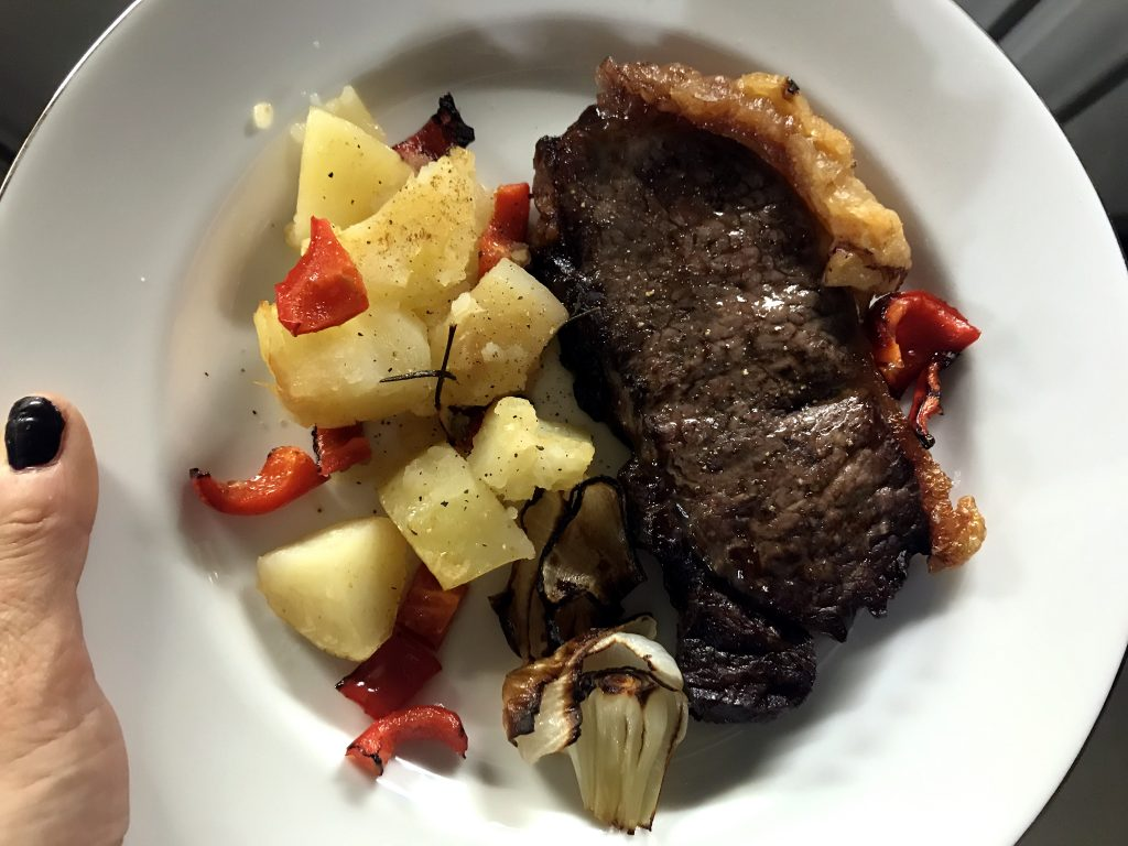 Hand holding a plate with steak and potatoes