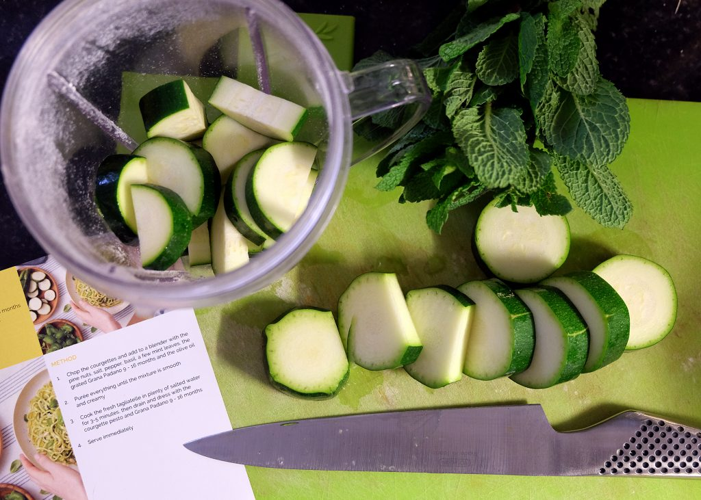 Chopping board with knife and courgette and mint